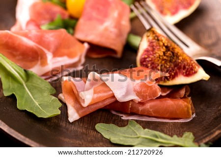 Prosciutto with figs and arugula closeup