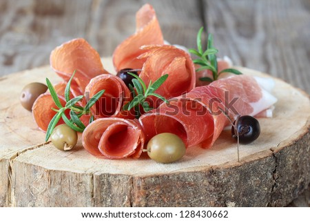 Prosciutto with olives and rosemary - stock photo