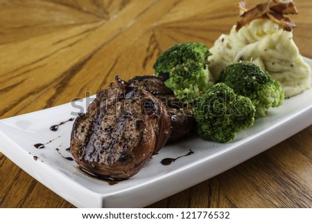 Prosciutto wrapped pork tenderloin grilled and served with mashed potato and broccoli nicely plated - stock photo