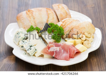 prossiutto with cheese and bread on white plate on brown wooden background