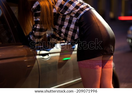 Prostitute in mini skirt looking into car - stock photo