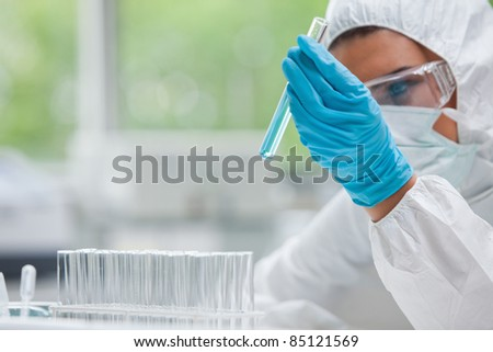 Protected science student holding a test tube in a laboratory - stock photo