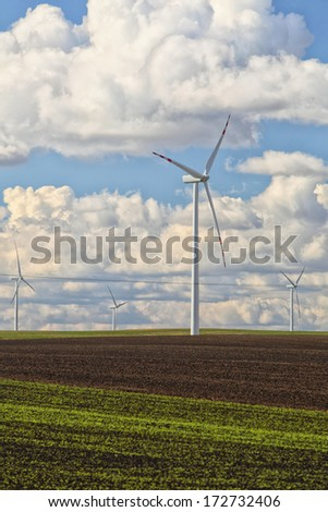Protection of nature. Wind turbines eco power generator for renewable energy production. Alternative green clean energy, ecology. Cloudy sky meadow. - stock photo