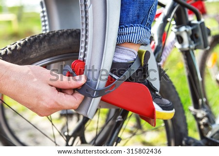 Protection on  bicycle. Hands of caucasian man is fastening security belt to child'??s legs, who is sitting in safety bike seat (chair). Toddler has a trip. Travel (vacation), transportation concept. - stock photo