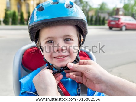Protection on the bicycle. Caucasian hands of father are putting biking helmet on outside to his son. The son is in the bicycle chair (seat) during bicycle ride. Travel, freedom, adventure  concept.   - stock photo