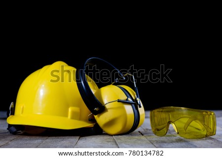 Protective clothing on a wooden workshop table. OSH accessories in the workshop. Black. background.