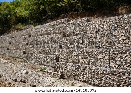 Protective gabion wall in mountains - stock photo