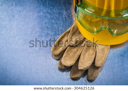 Protective leather gloves yellow building helmet and plastic safety eyewear on scratched metallic background top view construction concept. - stock photo