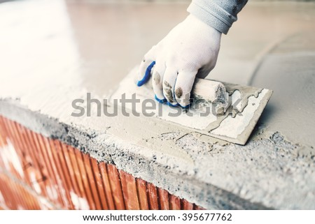 protective material against water on house building. worker waterproofing cement  - stock photo