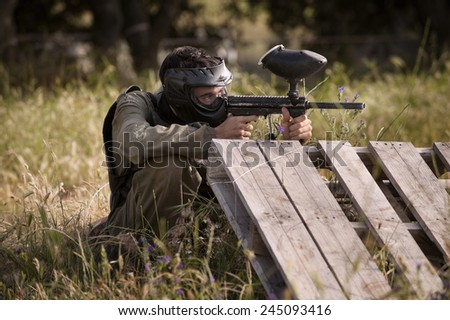 Protective sport player in uniform and mask Aiming gun - stock photo