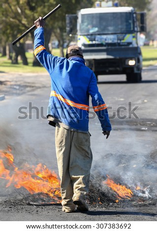 Protester burning rubber tyres in the streets in South Africa with police riot vehicle in background - stock photo
