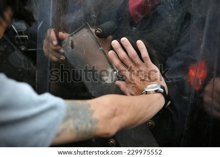 Protester Pushes Police Riot Shield - stock photo