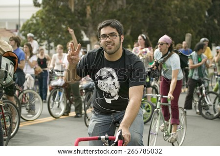 Protesters arrive on bicycle and give the peace sign at an anti-Iraq War protest march in Santa Barbara, California on March 17, 2007 - stock photo