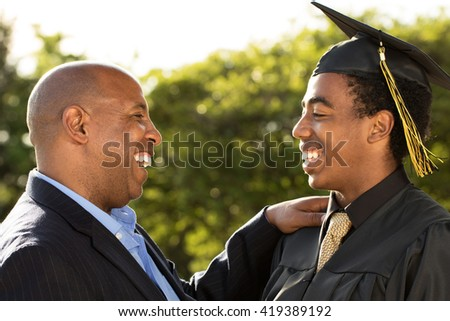 Proud African American father talking with his son. - stock photo