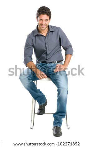 Proud and satisfied young man sitting on chair and looking at camera isolated on white background