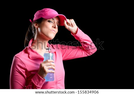 Proud and successful fitness girl in ping sportswear holding water bottle after exercising. Beautiful sportswoman success. Brunette caucasian sporty model. - stock photo