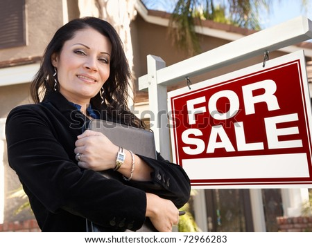 Proud, Attractive Hispanic Female Agent In Front of For Sale Real Estate Sign and House. - stock photo