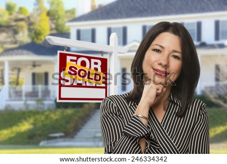 Proud, Attractive Hispanic Female Agent In Front of Sold For Sale Real Estate Sign and House. - stock photo