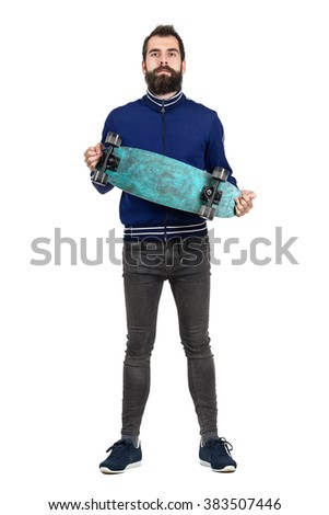 Proud bearded hipster carrying and showing skateboard to camera. Full body length portrait isolated over white studio background.  - stock photo