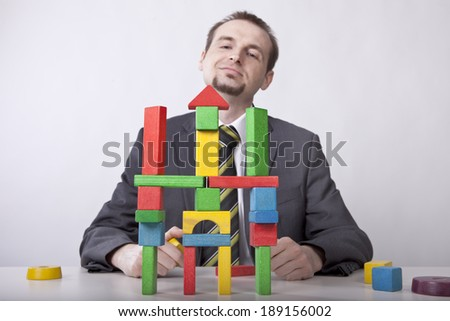 Proud businessman creates castle from toy's blocks in the office - stock photo