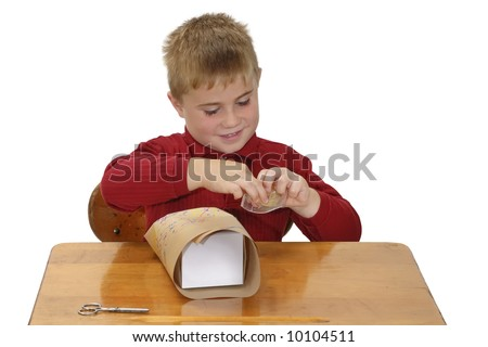 Proud child wrapping a gift with paper he colored - stock photo