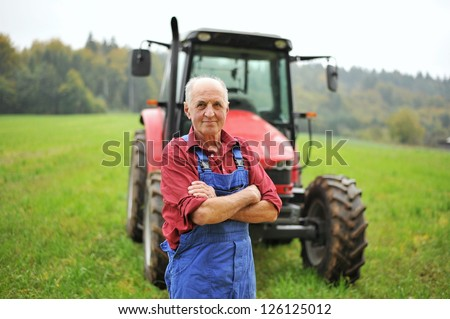 Proud farmer standing in front of his red tractor - stock photo