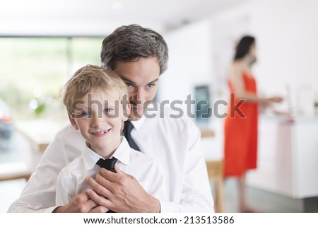 proud father helping his boy to put his tie - stock photo