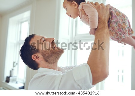 Proud father holding his newborn baby daughter up in the air at home - stock photo
