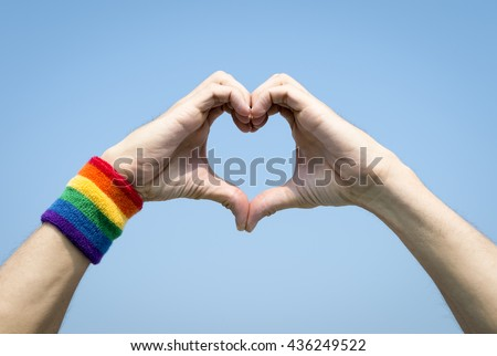 Proud gay hands making hand heart with rainbow colors wristband against bright blue sky - stock photo