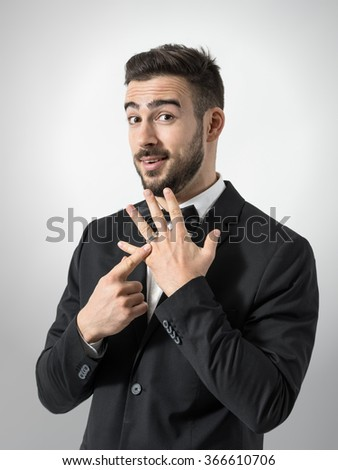 Proud happy groom pointing his wedding ring looking at camera. Portrait over gray studio background.  - stock photo