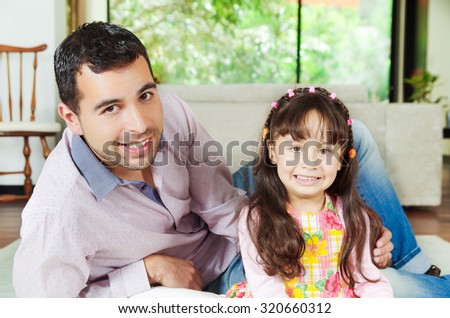 Proud hispanic father and adorable young girl posing together lying down and looking into camera smiling. - stock photo