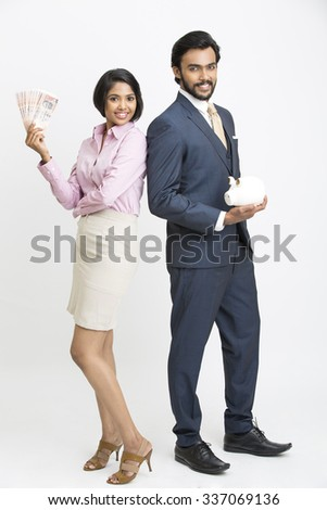 Proud Indian businessman holding piggy bank and standing with his colleague and she holding money on white background. - stock photo
