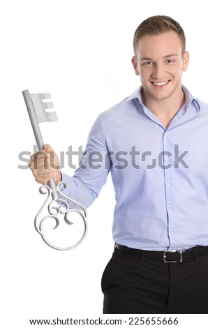 Proud isolated business man holding a key for a new house or symbol for career, luck and success. - stock photo