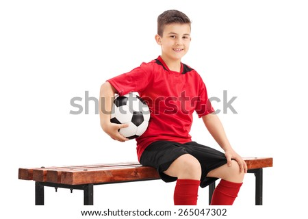 Proud junior football player posing seated on a wooden bench and holding a football in his hand isolated on white background - stock photo