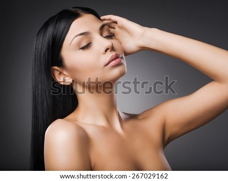Proud of her fresh and smooth skin. Beautiful young shirtless woman holding hand in hair and keeping eyes closed while standing against grey background   - stock photo