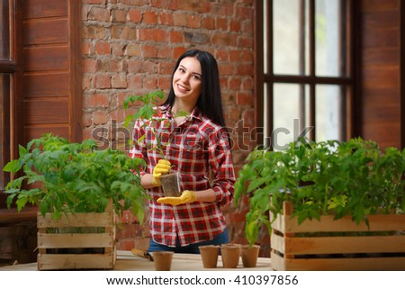 Proud of her gardening. Charming young brunette posing with a plant in a pot looking to the camera cheerfully.