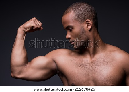 Proud of his perfect biceps.  Young shirtless African man looking at his biceps while standing against black background
