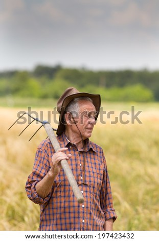 Proud old man farmer holding fork and looking at his field - stock photo