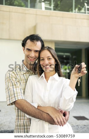 Proud owner of a new apartment: Couple holding keys - stock photo