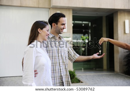 Proud owner of a new apartment: Couple receiving keys - stock photo