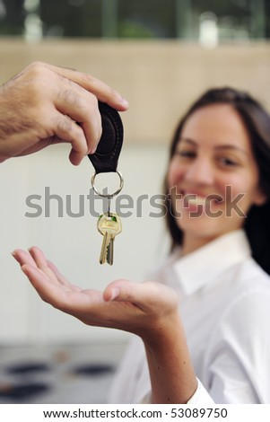 Proud owner of a new apartment: Woman receiving the keys - stock photo