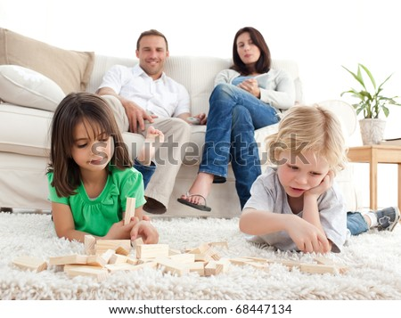 Proud parents looking at their children playing with dominoes on the floor of the living room - stock photo