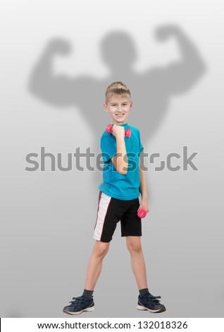 Proud slim boy with bodybuilder's silhouette behind him - stock photo