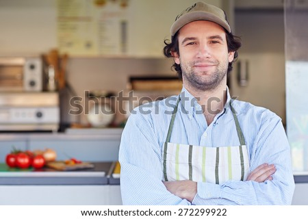 Proud small business owner standing in front of his business where he makes and sells takeaway food - stock photo