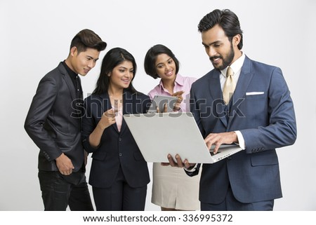 Proud smiling businessman working in laptop with his team business people on white. - stock photo