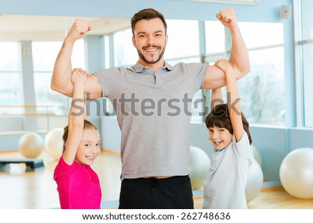 Proud to be strong. Cheerful young sporty father showing his biceps while children bonding to him and smiling  - stock photo
