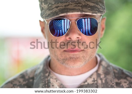 Proud us army soldier with american flag in sunglasses reflection. focus on glasses - stock photo