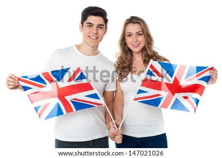 Proud young couple holding British flag - stock photo