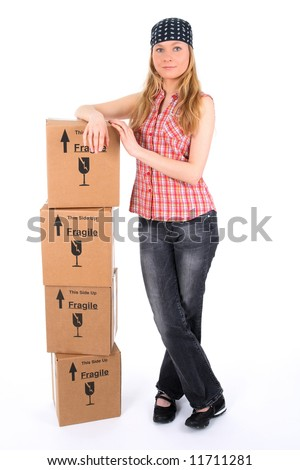 Proud young woman leaning against a stack of parcels. - stock photo