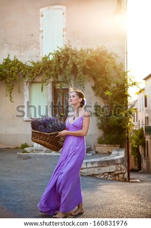 Provence, France. Tiny town of Sault. Girl with a basket of freshly cut lavender in the old city. Today Sault is lavender capital of Provence. Every year in august in the town start Lavender Festival. - stock photo